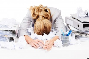 A young businesswoman lying face down in a pile of crumpled documents at her desk